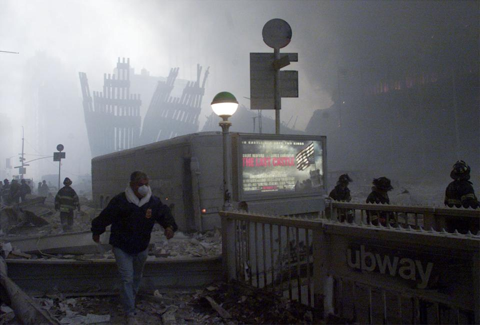 <p>The wreck of the World Trade Center smolders in the background as a man passes a subway stop near the World Trade Center Towers after planes crashed into each of the buildings in New York. (Reuters)</p>