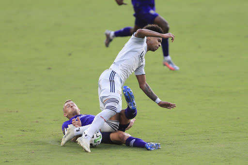 Orlando City defender Robin Jansson, bottom, slide-tackles New England Revolution forward Tajon Buchanan (17) during the second half of an MLS playoff soccer match, Sunday, Nov. 29, 2020, in Orlando, Fla. (AP Photo/Matt Stamey)
