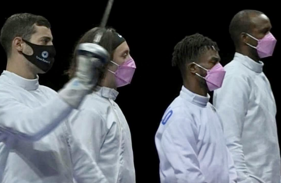 Three members of the U.S. fencing team wore pink masks as a show of support for victims, while their teammate, accused of sexual misconduct, looked on. (Photo Credit: Twitter/@IbtihajMuhammad)