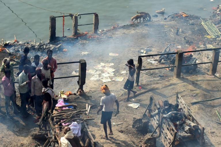 A young boy (R) looks for discarded clothes used to wrap dead bodies for final rites for money, at a cremation site in Varanasi, India
