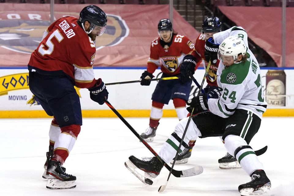 Dallas Stars left wing Roope Hintz (24) passes the puck as Florida Panthers defenseman Aaron Ekblad (5) defends during the third period of an NHL hockey game, Monday, Feb. 22, 2021, in Sunrise, Fla. The Panthers won 3-1. (AP Photo/Lynne Sladky)