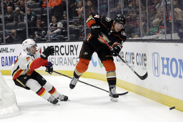 Anaheim Ducks' Cam Fowler, right, hits the puck as Calgary Flames' Austin Czarnik approaches during the first period of an NHL hockey game Sunday, Oct. 20, 2019, in Anaheim, Calif. (AP Photo/Marcio Jose Sanchez)