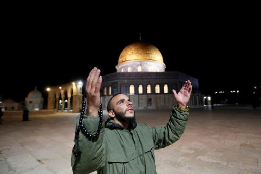 A man prays in front of the Dome of the Rock at the Al-Aqsa mosque compound, which reopened on Sunday