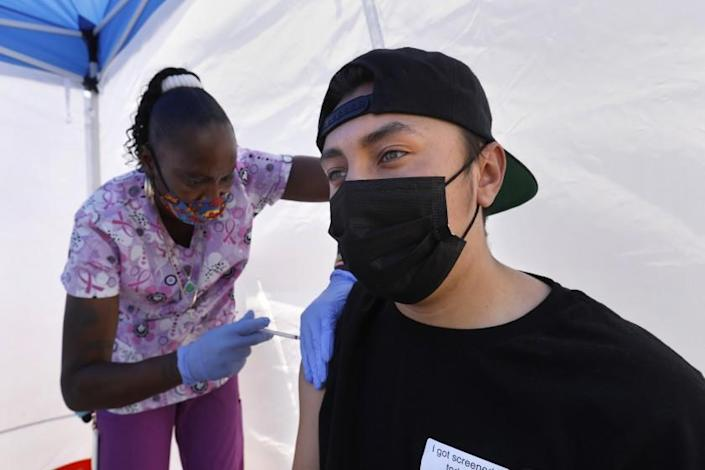 Los Angeles, California—May 12, 2021—At the East Los Angeles Civic Center, St. John's Well Child & Family Center runs a vaccine clinic. Tanya Mitchell, a certified medical assistant, left, administers his a vaccinate to Richard Ayala, age 18, on California on May 12, 2021. (Carolyn Cole / Los Angeles Times)