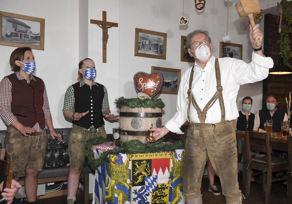 Christian Ude, Honorary Citizen of the City of Munich and former Mayor of Munich, taps the first barrel at the tapping in the Schillerbräu with a mouth and nose protector in Munich, Germany, Saturday, Sept.19, 2020. Despite the cancellation of the Wiesn due to Corona, events and actions take place in the state capital. (Felix Hörhager/dpa via AP)