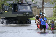 Michael Thomas, back, carries his daughter Mikala, out of his flooded neighborhood while a high water rescue vehicle moves past after Hurricane Ida moved through Monday, Aug. 30, 2021, in LaPlace, La. (AP Photo/Steve Helber)
