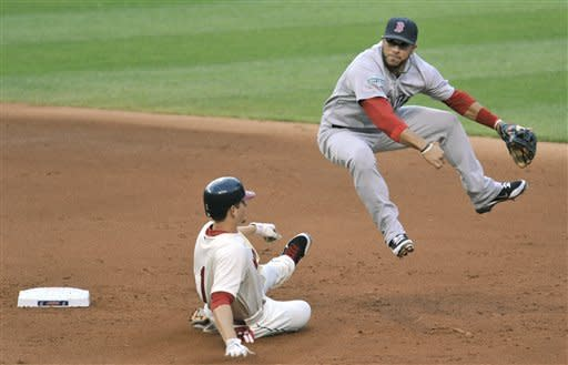 Boston Red Sox shortstop Mike Aviles, right, leaps over Cleveland Indians' Brent Lillibridge after forcing him out on a fielder's choice in the fifth inning of a baseball game on Saturday, Aug. 11, 2012, in Cleveland. (AP Photo/David Richard)