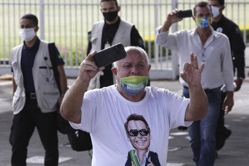 A supporter of Brazil's President Jair Bolsonaro, wearing a face mask amid the new coronavirus pandemic and a T-shirt covered in pro-Bolsonaro messages, yells against journalists after the president's departure from his official residence of Alvorada palace in Brasilia, Brazil, Monday, May 25, 2020. (AP Photo/Eraldo Peres)