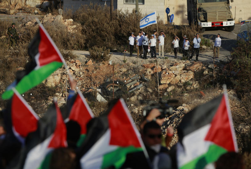 Israeli Jewish settlers hold an Israeli flag while Palestinian protesters wave Palestinian flags during a protest against the Prawer Plan to resettle Israel's Palestinian Bedouin minority from their villages in the Negev Desert, near the Israeli settlement of Bet El, north of the West Bank city of Ramallah, Saturday, Nov. 30, 2013. (AP Photo/Majdi Mohammed)