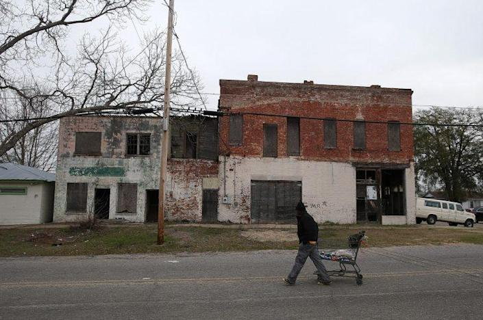 A pedestrian pulls a shopping cart by vacant buildings on March 6, 2015, in Selma, Ala. (Photo: Justin Sullivan/Getty Images)