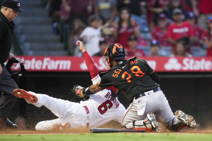 Los Angeles Angels' Anthony Rendon (6) is safe at home to scored ahead of a tag by Baltimore Orioles catcher Pedro Severino (28) during the third inning of a baseball game Friday, July 2, 2021, in Anaheim. (AP Photo/Ashley Landis)