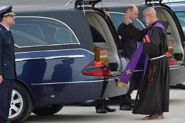 A priest blesses the coffins of the Italian victims of the Tunis museum attack at Ciampino airport in Rome after they were repatriated on March 21, 2015 (AFP Photo/Andreas Solaro)