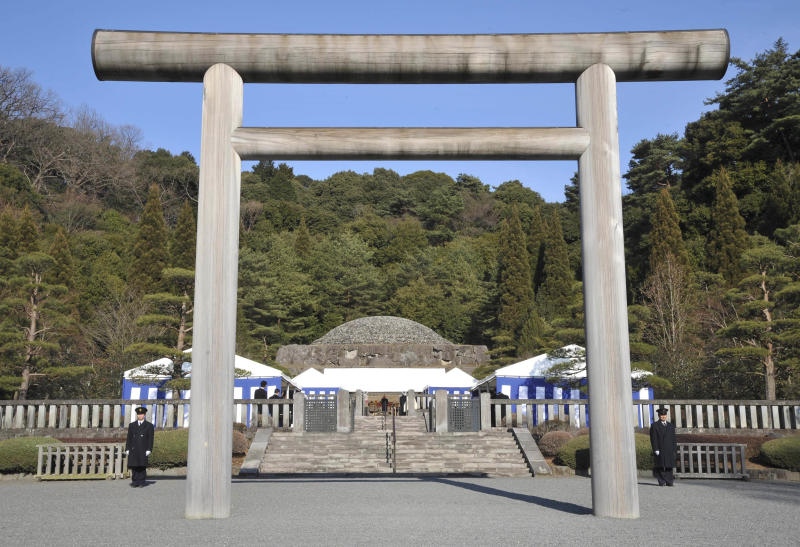 "FILE - In this Jan. 7, 2009 file photo, security officers stand guard near a ""torii"" gate as Japan's Emperor Akihito, center, offers prayers at Musashino Imperial Mausoleum in Hachioji in the western suburbs of Tokyo, marking the 20th anniversary of late Emperor Hirohito's death. Akihito, turning 80 on Monday, Dec. 23, 2013 is still active, making an official visit to India in November with his wife, the 79-year-old Empress Michiko. But concerns have grown since he had heart bypass surgery nearly two years ago on top of prostate cancer earlier. After an expert panel discussion for more than a year, the palace announced that Akihito will be cremated, and his remains placed in a mausoleum smaller than those of his predecessors, with Michiko's by his side at the Imperial compound in western Tokyo. Akihito's cremation breaks a 400-year burial custom of the world's oldest monarchy, as he wishes to trim cost, space and burden on the people, officials said. (AP Photo/Katsumi Kasahara, File)"