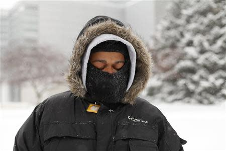 A man waits for a transit bus in several inches of snow in Detroit, Michigan January 2, 2014. REUTERS/Joshua Lott