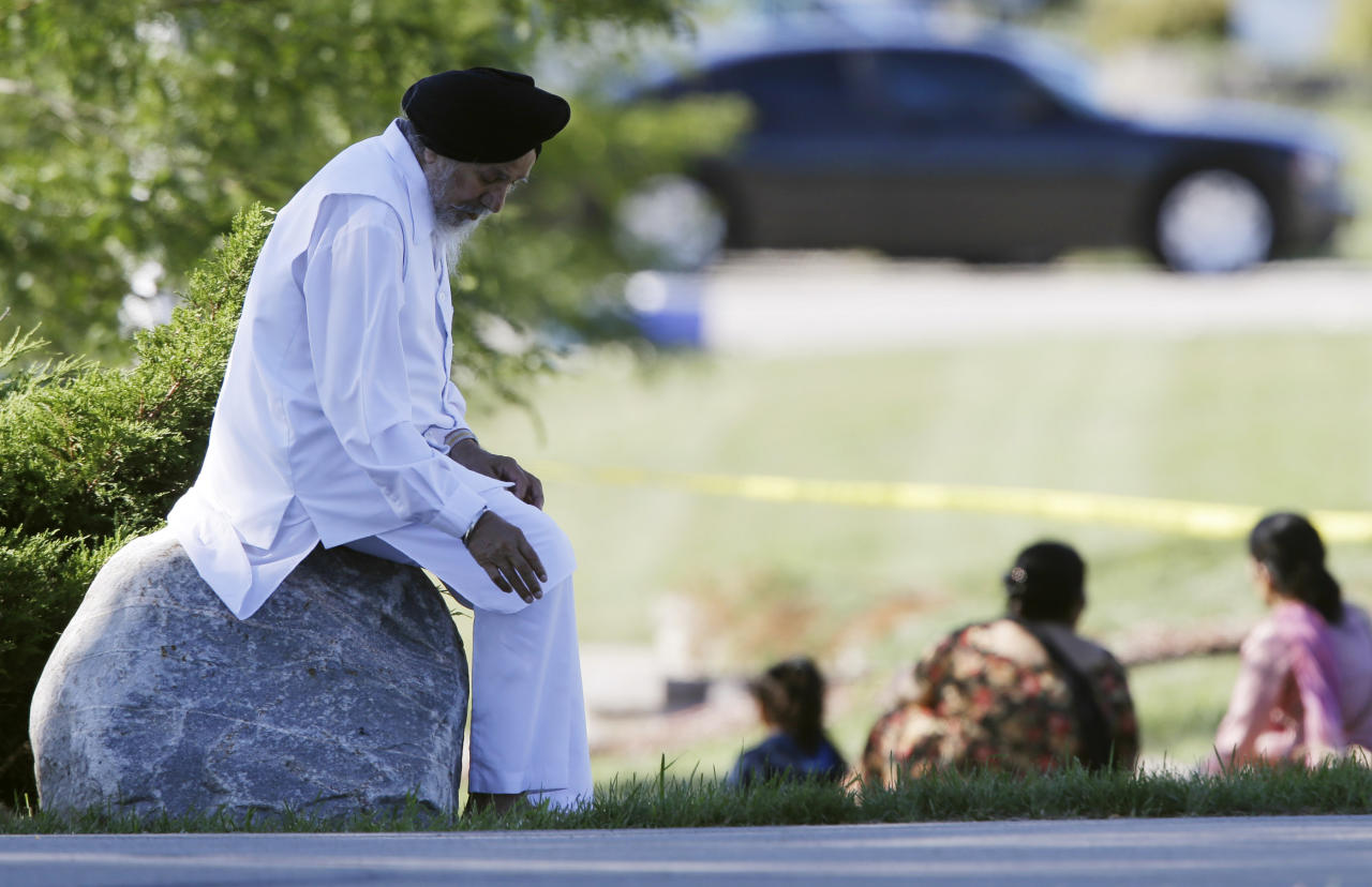 A man sits on a rock as police investigate the Sikh Temple of Wisconsin in Oak Creek, Wis., after a shooting Sunday, Aug 5, 2012. A gunman killed six people at the suburban Milwaukee temple in a rampage that left terrified congregants hiding in closets and others texting friends outside for help. The suspect was killed outside the temple in a shootout with police officers. (AP Photo/Jeffrey Phelps)