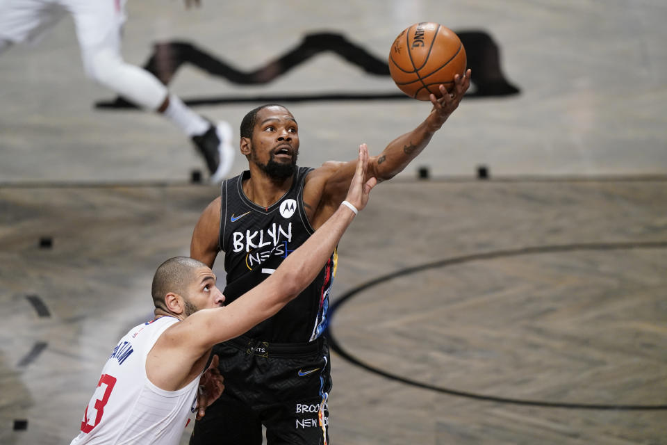 Los Angeles Clippers forward Nicolas Batum defends Brooklyn Nets forward Kevin Durant as Durant reaches for the ball.