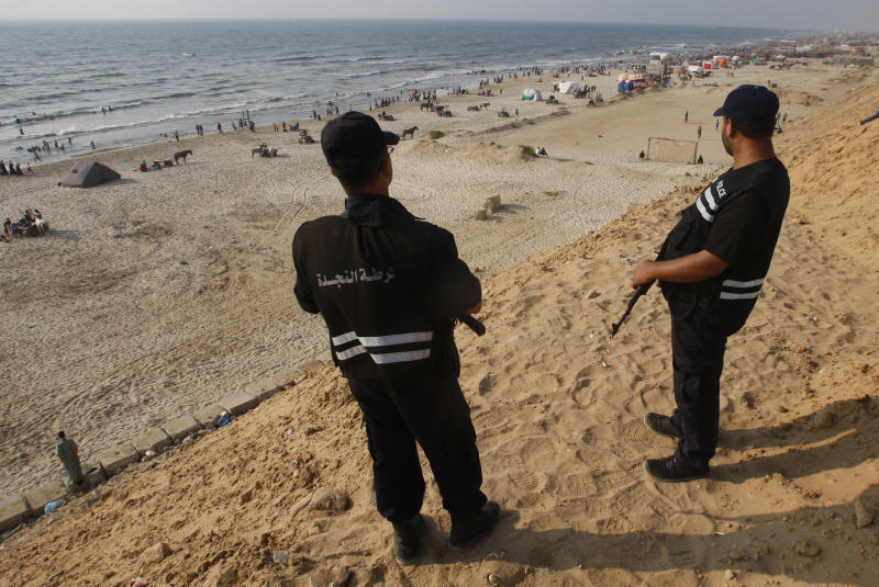 "Palestinian security police officers secure the main beach as people bathe in the Mediterranean sea in Gaza City, Friday, June 22, 2012. In five years, the Islamist group Hamas has established a functioning but authoritarian and highly entrenched statelet with a strong Islamic flavor in Gaza. Having come to power as a ""clean"" alternative to corrupt secular rivals, the Palestinian Islamists have lost much of that luster among Gazans who are even poorer and even more despondent now. It's an embarrassment for their parent group, the Muslim Brotherhood, as it vies for power in a tense electoral standoff in neighboring Egypt. (AP Photo/Hatem Moussa)"