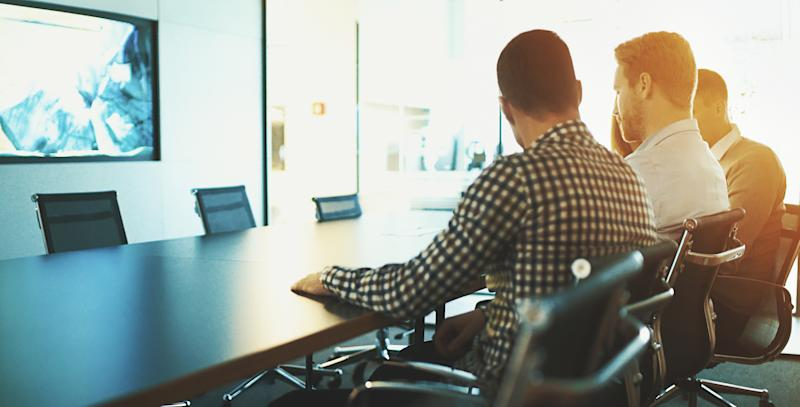 Closeup rear view of four coworkers having a brief meeting at conference room.One of the colleagues is showing something on his smartphone but it's not visible in the frame. Back lit with sunlight, copy space.