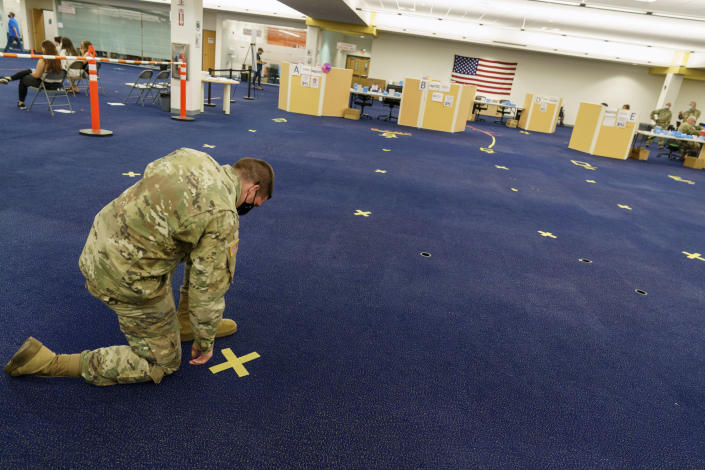 Rhode Island Army National Guard Staff Sgt. Andrew Bates pulls up tape marking a line at a coronavirus mass-vaccination site at the former Citizens Bank headquarters in Cranston, R.I., Thursday, June 10, 2021. The U.S. is confronted with an ever-growing surplus of COVID-19 vaccines, looming expiration dates and stubbornly lagging demand at a time when the developing world is clamoring for doses to stem a rise in infections. (AP Photo/David Goldman)
