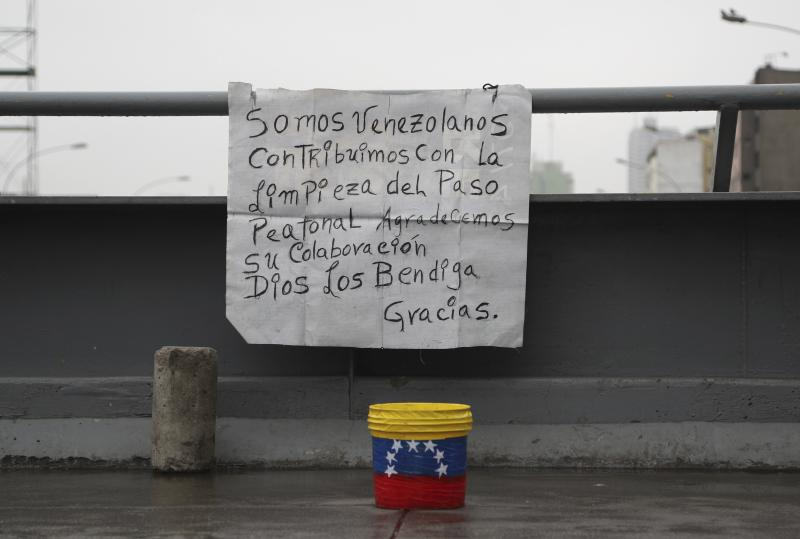 """In this Oct. 8, 201 photo, a sign asking for money in exchange for keeping a bridge clean hangs in Lima, Peru. The sign reads in Spanish """"We are Venezuelans. We contribute to the cleaning of this pedestrian pass. We appreciate your collaboration. May God bless you. Thank you."""" (AP Photo/Martin Mejia)"""