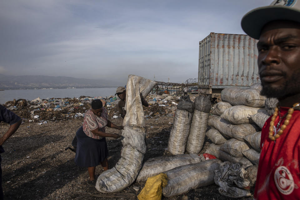 A woman packs charcoal to sell at a market in downtown Port-au-Prince, Haiti, Wednesday, Sept. 22, 2021. Deportees join thousands of fellow Haitians who have been displaced from their homes, pushed out by violence to take up residence in crowded schools, churches, sports centers and makeshift camps among ruins. (AP Photo/Rodrigo Abd)
