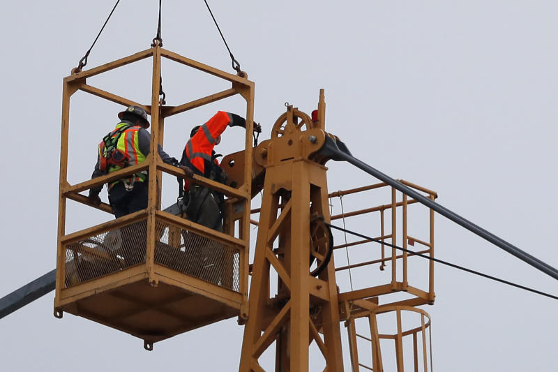 Workers in a bucket hoisted by a crane begin the process of preparing the two unstable cranes for implosion at the collapse site of the Hard Rock Hotel, which underwent a partial, major collapse while under construction last Sat., Oct., 12, in New Orleans, Friday, Oct. 18, 2019.  Plans have been pushed back a day to bring down two giant, unstable construction cranes in a series of controlled explosions before they can topple onto historic New Orleans buildings, the city's fire chief said Friday, noting the risky work involved in placing explosive on the towers.