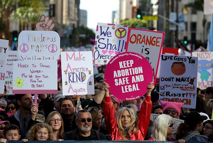 <p>Participants hold signs as they march during the Women's March on January 21, 2017 in Los Angeles, California. (Photo by Justin Sullivan/Getty Images) </p>