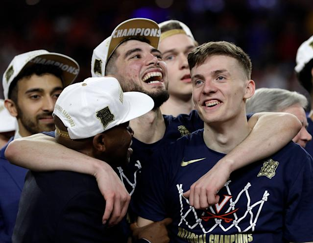Virginia's Ty Jerome, center, and Kyle Guy, right, celebrate after defeating Texas Tech 85-77 in the overtime in the championship of the Final Four NCAA college basketball tournament, Monday, April 8, 2019, in Minneapolis. (AP Photo/David J. Phillip)