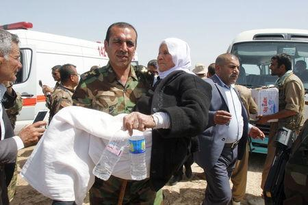 An officer from the Kurdish forces carries an elderly woman from the minority Yazidi sect, on the outskirts of Kirkuk April 8, 2015. REUTERS/Ako Rasheed