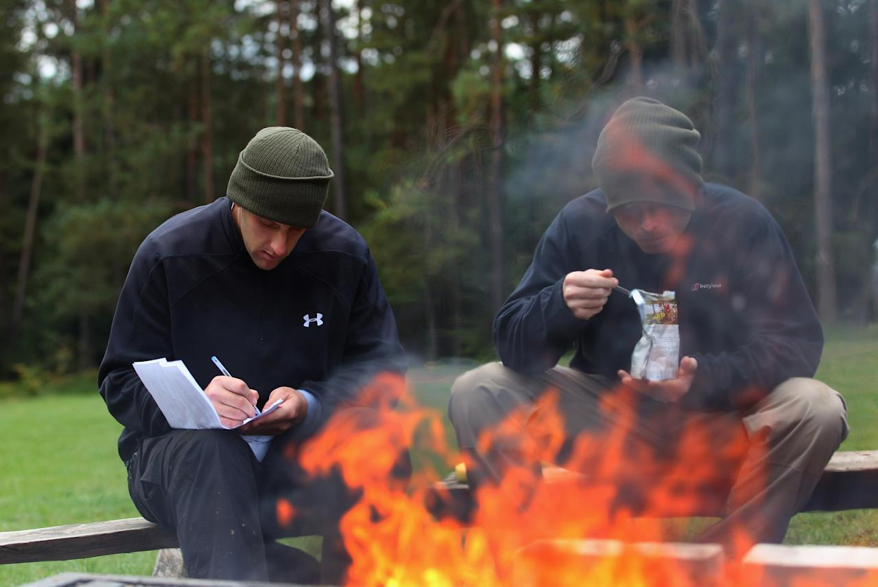 NUREMBERG, GERMANY - SEPTEMBER 26:  England players James Tredwell and  Ian Bell by the camp fire at the England Cricket squad Pre Ashes Training Camp on September 26, 2010 near Nuremberg, Germany.  (Photo by Stu Forster/Getty Images)