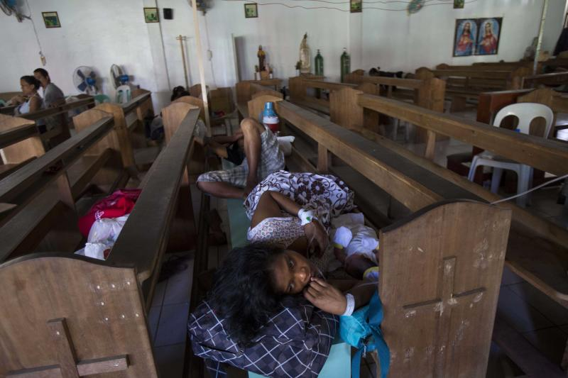 A mother rests in a church pew with her newborn baby in a Catholic chapel inside the Eastern Visayas Regional Medical Center in Tacloban on Saturday Nov. 16, 2013. The chapel is now being used to care for infants after Typhoon Haiyan destroyed the original facility of the hospital. (AP Photo/David Guttenfelder)