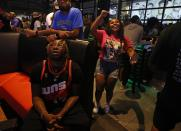 People watch television coverage of the Milwaukee Bucks and Phoenix Suns playing in Game 6 of the NBA basketball finals, Tuesday, July 20, 2021, in Milwaukee. The Bucks won the championship. (AP Photo/Jeffrey Phelps)