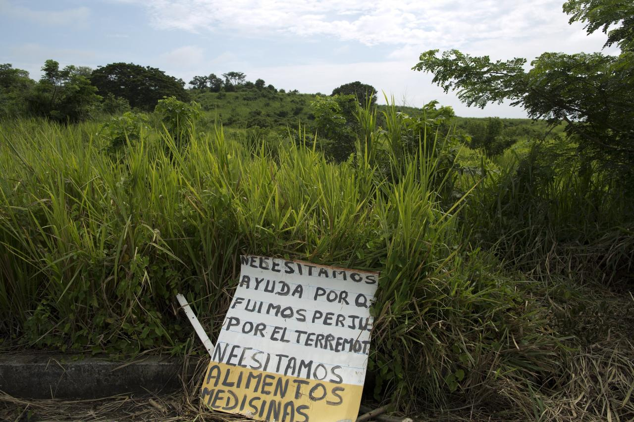 "This April 25, 2016 photo shows a sign that reads in Spanish; ""We need help because we were affected by the earthquake, we need food and medicine,"" on the side of a highway outside Pedernales, Ecuador. More than a dozen roads were closed due to damage from th April 16, 7.8-magnitude earthquake, making it harder for rescuers to reach where they were needed most. (AP Photo/Rodrigo Abd)"