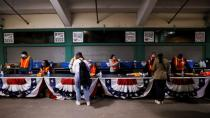 Voters pick up their ballots at Fenway Park on the first day of early voting in Boston
