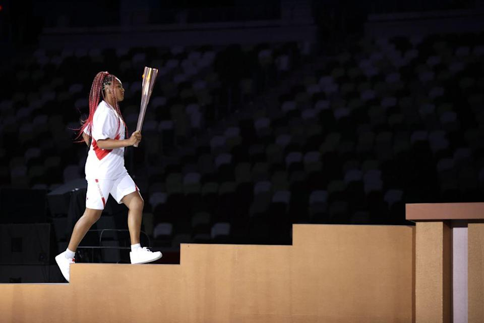 Naomi Osaka carries the Olympic Torch during the opening ceremony in the Olympic Stadium at the 2020 Summer Olympics, Friday, July 23, 2021, in Tokyo, Japan. - Credit: AP
