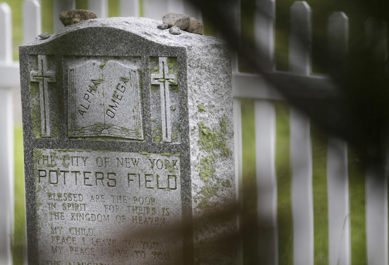 """FILE - This May 23, 2018, file photo, shows a stone marker proclaiming """"The City of New York Potters Field,"""" a burial ground on Hart Island in New York. New York City's mayor signed a bill on Wednesday, Dec. 4, 2019, that transfers control of the nation's largest public burial ground from the correction department to the parks department. (AP Photo/Seth Wenig, File)"""