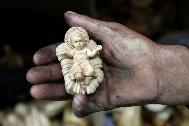 Palestinian worker holds a figurine carved from olive wood, to be sold during Christmas season, at a workshop in Bethlehem in the Israeli-occupied West Bank