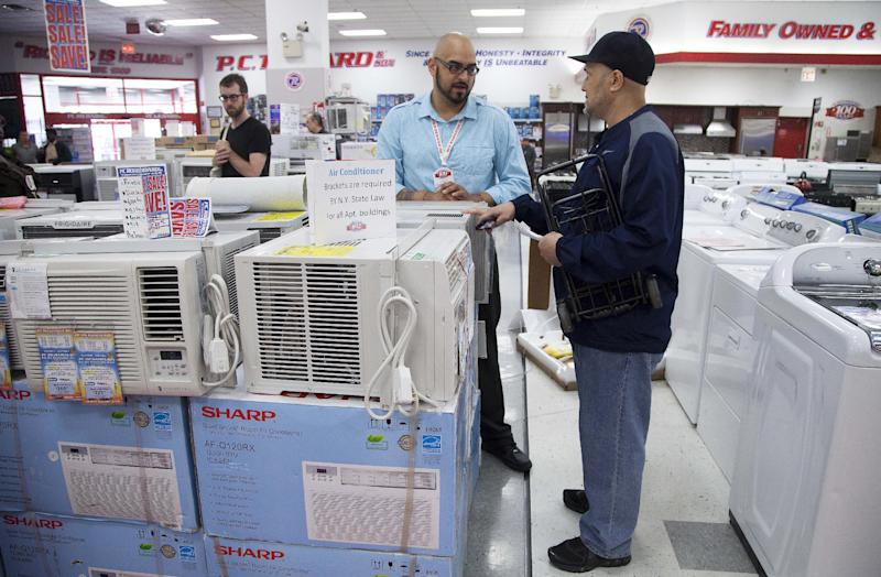 Salesman Carlos Burgos, center, helps customer Raven Campbell, right, select an air conditioner at P.C. Richard & Son, an electronics and appliance store, Tuesday, June 19, 2012 in the Brooklyn borough of New York. Temperatures are expected to approach or top 100 degrees Wednesday and Thursday in cities including New York, Philadelphia and Boston. (AP Photo/Mark Lennihan)