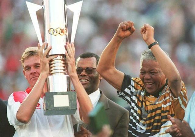 South Africa captain Neil Tovey (L) holds the Africa Cup of Nations trophy after the 1996 final while then President Nelson Mandela (R) celebrates (AFP Photo/Mykel NICOLAOU)