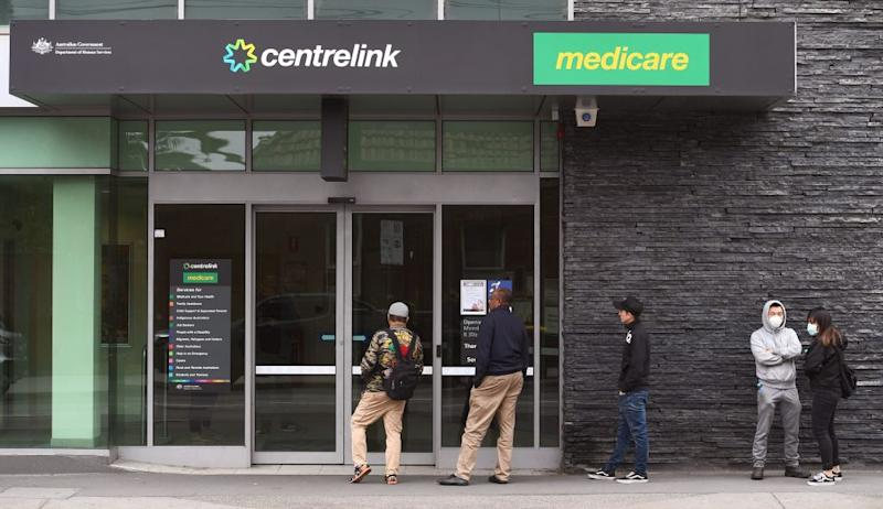 People queue outside an Australian government welfare centre, Centrelink, in Melbourne on March 23, 2020. (Photo by William WEST / AFP) (Photo by WILLIAM WEST/AFP via Getty Images)