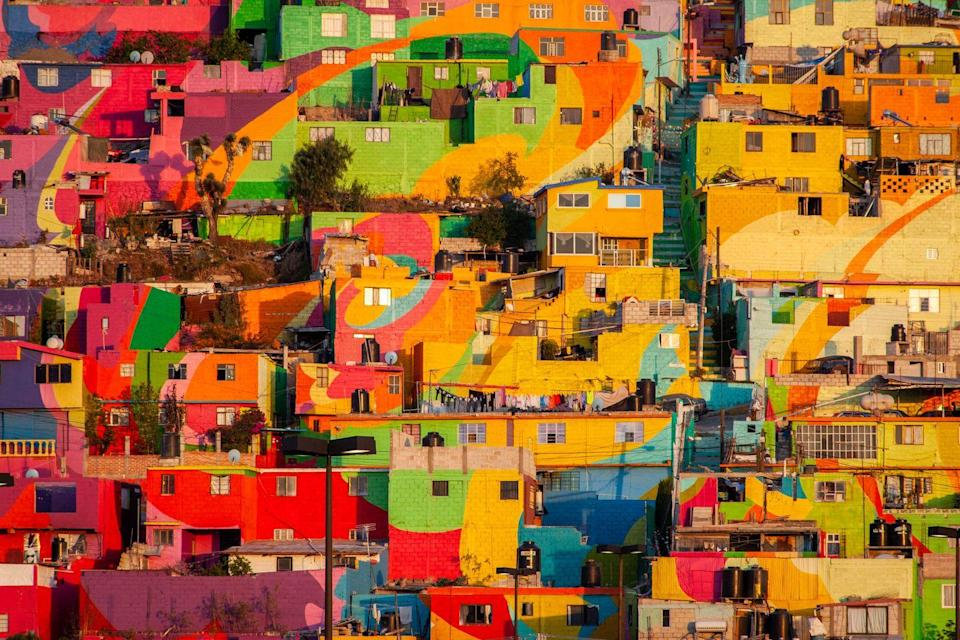 <p>The story of how Las Palmitas became so colorful is a story of community. Pachuca's hillside neighborhood once was considered an impoverished area with high crime rates. That was until a group of government-funded artists, led by Enrique Gómez, began to turn the cluster of homes into a giant work of art while helping the locals find jobs. The muralists and residents worked together to paint 209 buildings in swirling patterns, with a few also displaying portraits of the locals. Since the mural's completion, the small Mexican neighborhood has risen to international fame, as well as turned into a place filled with community spirit.</p>