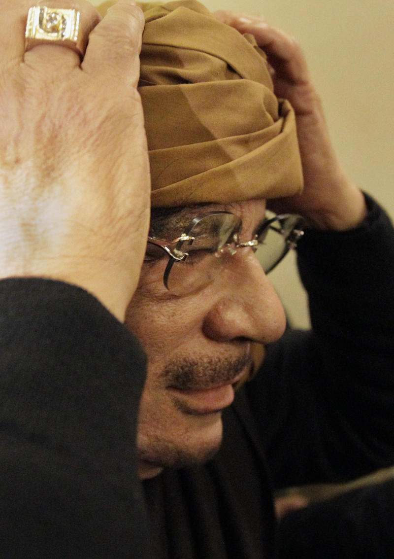 EDS NOTE: RECROP OF ABC102 Libyan Leader Moammar Gadhafi arrives at a hotel to give television interviews in Tripoli, Libya Tuesday, March 8, 2011. (AP Photo/Ben Curtis)