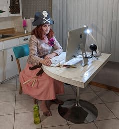 A woman in a pirate hat with pink hair sits in front of a desktop computer in a kitchen.