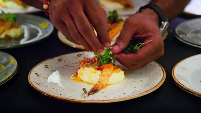 A pair of hands arranges a plate of food.