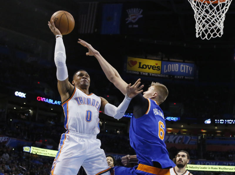 Oklahoma City Thunder guard Russell Westbrook (0) shoots over New York Knicks forward Kristaps Porzingis (6) during the first quarter of an NBA basketball game in Oklahoma City, Wednesday, Feb. 15, 2017. (AP Photo/Sue Ogrocki)