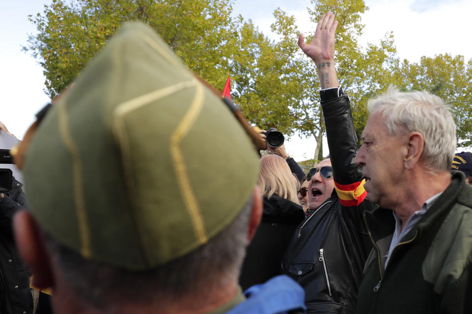 """A man makes the fascist salute outside Mingorrubio's cemetery, outskirts of Madrid, Thursday, Oct. 24, 2019. Forty-four years after his demise, the remains of Spanish dictator Gen. Francisco are to be dug out of his grandiose resting place outside Madrid and taken to a small family crypt, finally satisfying a long-standing demand of his victims' relatives and others who suffered under his regime. Inscription at ribbons reads in Spanish """"Barcelona always with Franco"""". (AP Photo/Manu Fernandez)"""