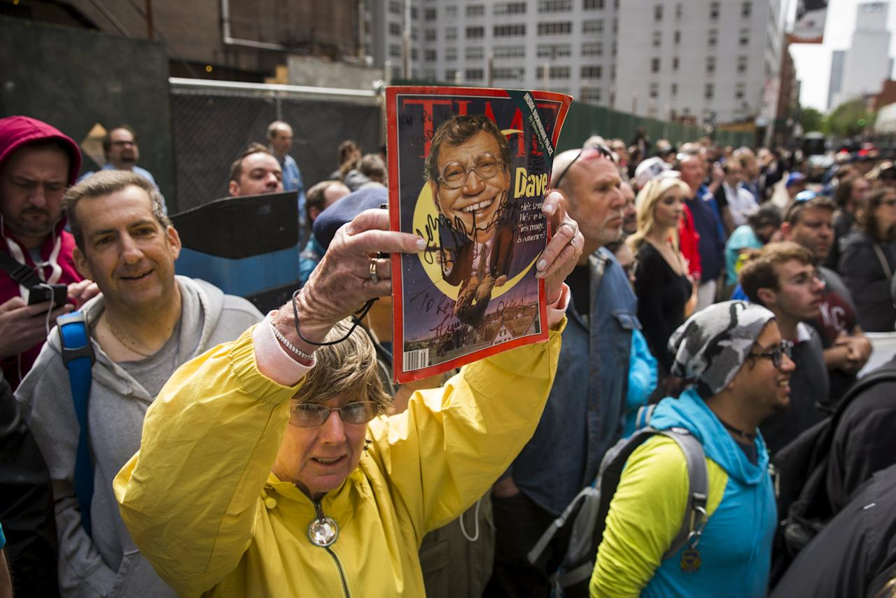 """A fan holds up a magazine with David Letterman's face on it outside of Ed Sullivan Theater in Manhattan as Letterman prepares for the taping of tonight's final edition of """"The Late Show"""" in New York May 20, 2015.  REUTERS/Lucas Jackson"""
