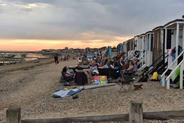 People sit on the beach into the evening as the sun set on Saturday in Southend-on-Sea.