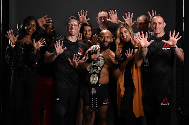 UFC flyweight champion Demetrious Johnson poses for a post fight portrait backstage with his team during the UFC Fight Night event at Sprint Center on April 15, 2017 in Kansas City, Missouri. (Getty Images)
