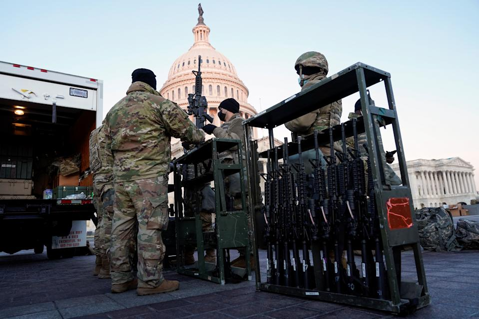Members of the National Guard are given weapons at the back of an open truck in front of the Capitol